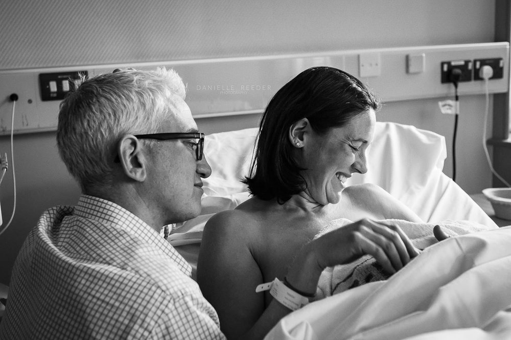 Mother and father both smiling as they admire their newborn daughter.