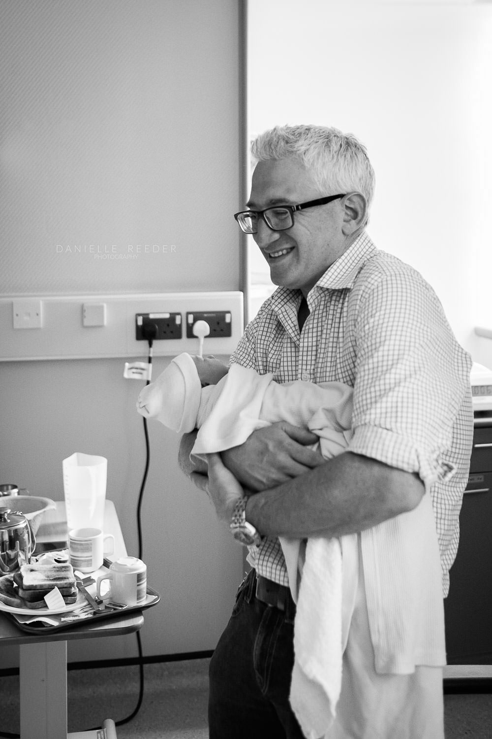 Father stood laughing as he craddles his newborn daughter.