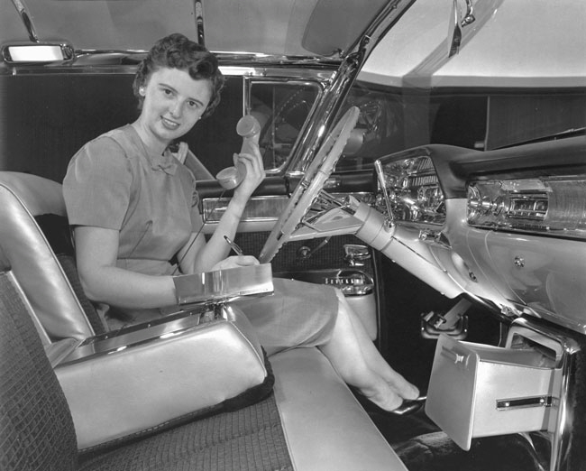 Vanderbilt demonstrating an early car phone and built-in memo pad—custom features for her 1958 exhibition-model Cadillac Eldorado Seville