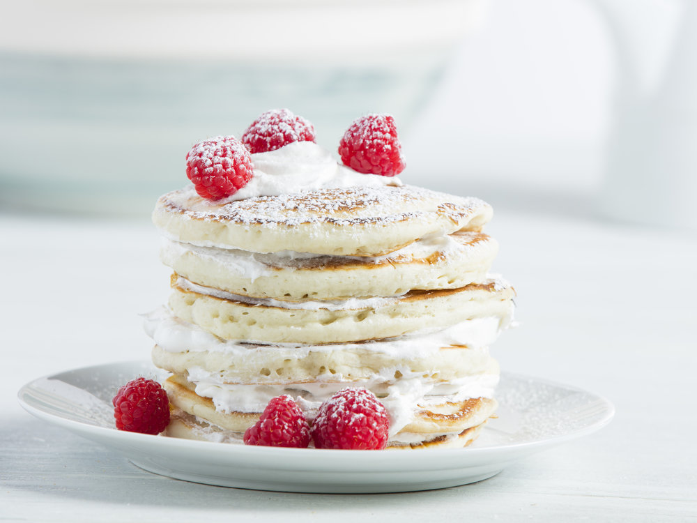 Stack of pancakes with raspberries in white kitchen
