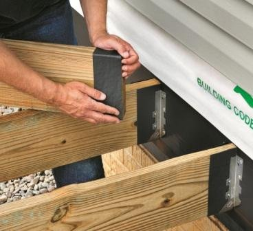 Wrap the ends of the joists with DeckWrap to create a barrier between the galvanized hardware and the ACQ-treated lumber.