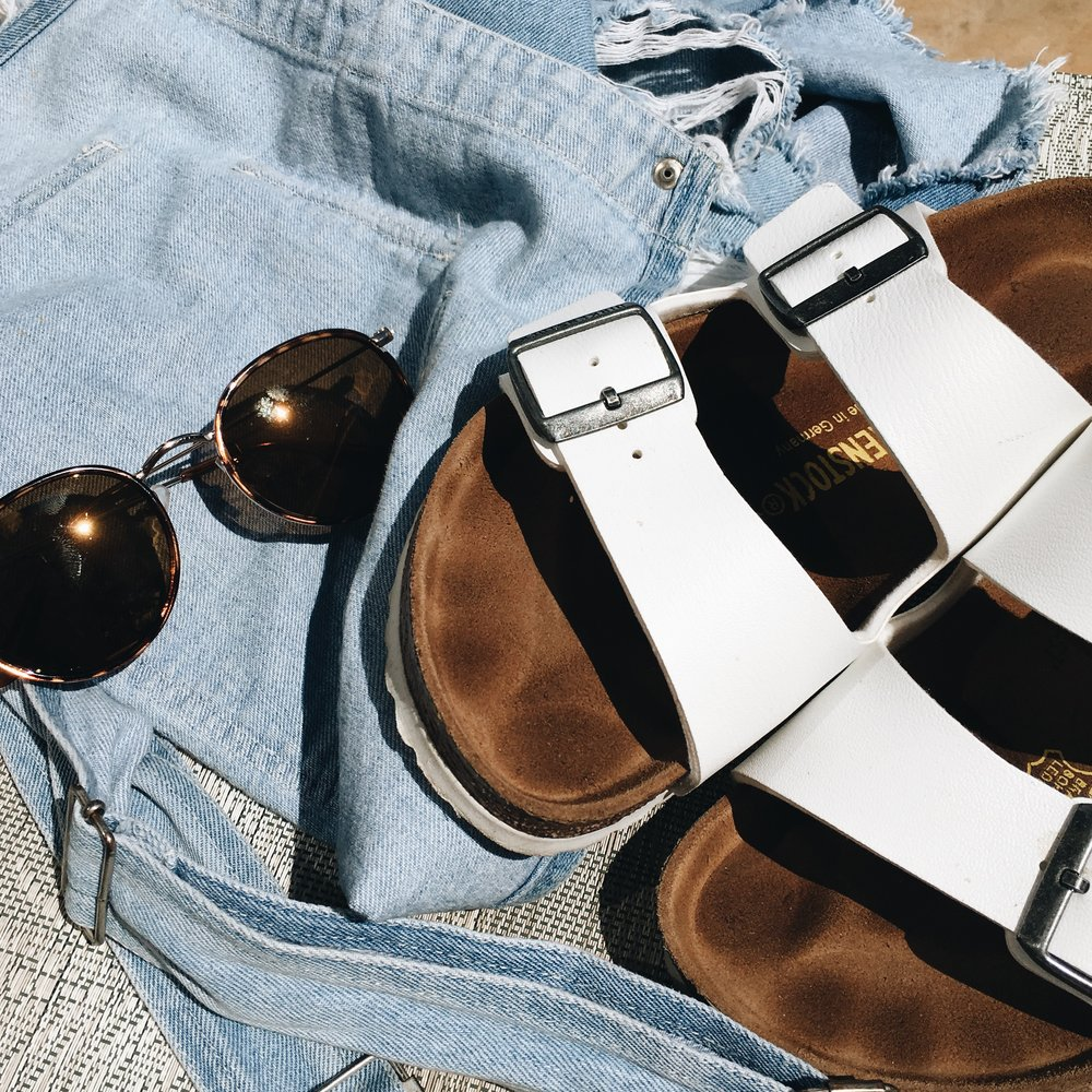 By Julia Baldwin  Whether you're jetting off to the Caribbean, driving down to Miami, or just staying in your home town--there are a few items essential to any vacation. You'll definitely need a pair of cute and comfortable sandals, such as the white Birkenstock slip-on sandals pictured. You'll also want to have a pair of sunglasses that are both protective to your eyes and fashionable. Don't forget a beach coverup--such as t-shirt dress or overalls!