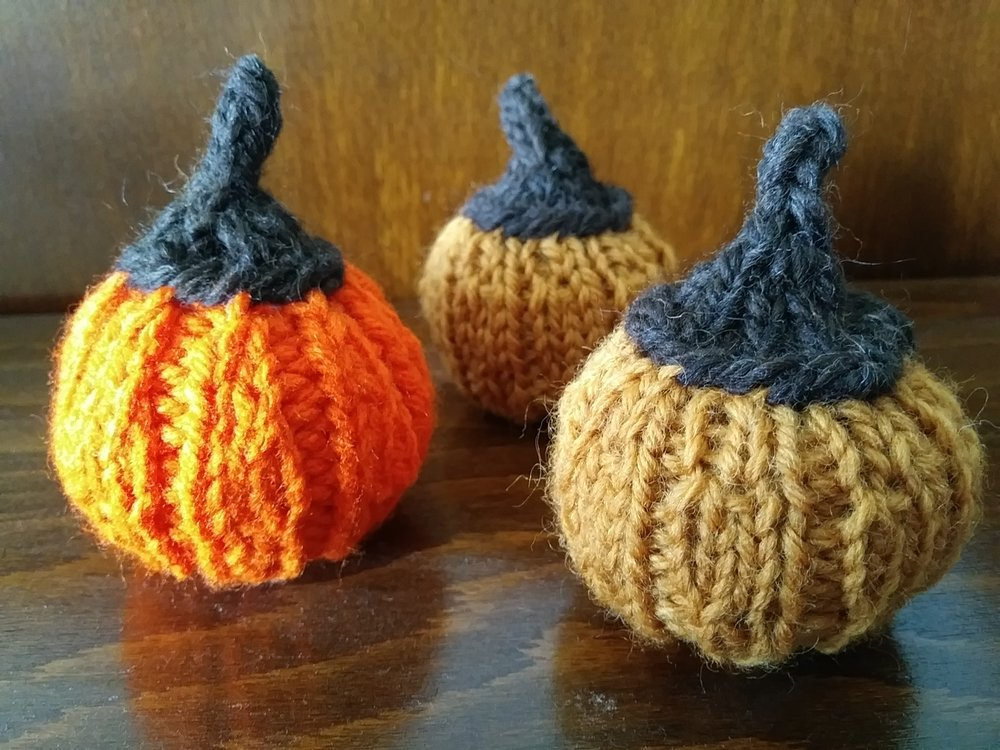 Pumpkins - Gauge does not matter for this pattern. Feel free to use scrap yarn.Using 4 double pointed needles, cast on 18 sts (6 sts per DPN).*K1, p1, repeat from* to last stitch.Repeat for 1 row.*Kfb, P1, repeat from* to last stitch.*K2, p1, repeat from* to last stitch.Repeat for 1 row.*Kfb, k1, P1, repeat from* to last stitch.*K3, p1, repeat from* to last stitch.Repeat for 2 rows.*K2tog, k1, P1, repeat from* to last stitch.*K2, P1, repeat from* to last stitch.Repeat for 1 row.*K2tog, P1, repeat from* to last stitch. Repeat for 1 row.K2tog all around.K3tog all aroundThread darning needle through remaining stitches. Pull tight and tie off. Using a tapestry needle, weave in all ends.StemCast on 16 sts (4 sts per DPN).K1 row in round.K2tog all around.K1 row in round.K3tog all around.K3sts onto 1 needle.K3 rows flat like i-cord.Bind off knitwise. Sew stem onto the pumpkin. Using a tapestry needle, weave in all ends.