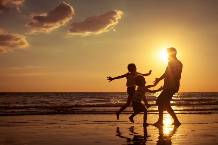 Family holding hands running to sunrise on a beach
