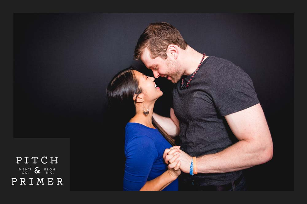 An example photo of a custom brand experience by Taco Photo Booth Co. The photo shows a fun loving couple holding hands.