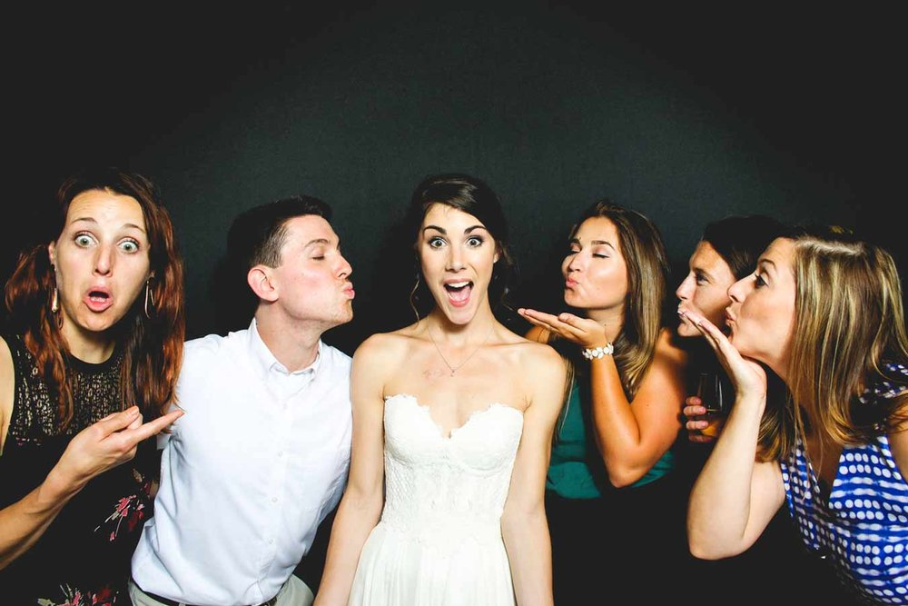 bride-and-friends-having-fun-in-black-backdrop-photo-booth