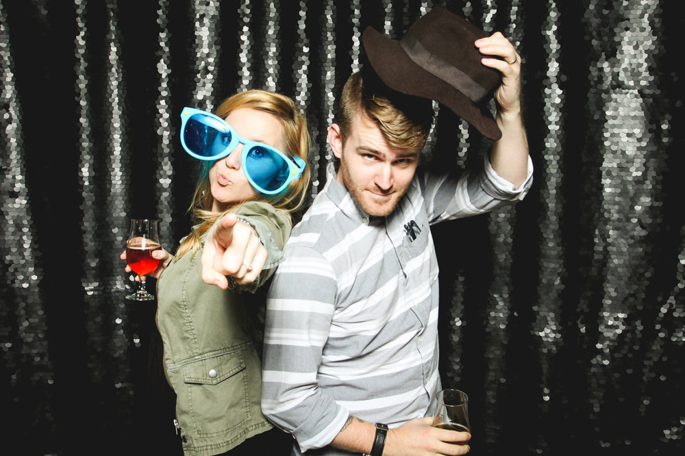 Young couple having fun in a photo booth, wearing some funky props, and standing in front of a beautiful black sequin backdrop.