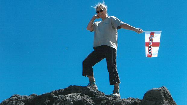 energy: Linda Hart celebrates climbing Mt Taranaki with some enthusiastic flag-waving. Will she do likewise when she completes the Camino de Santiago in Spain?