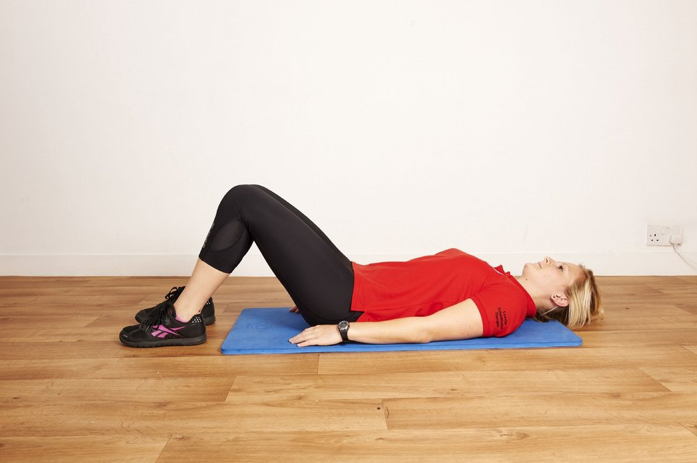 Step one of the back appeasing exercise  - lie flat on your back on a firm surface