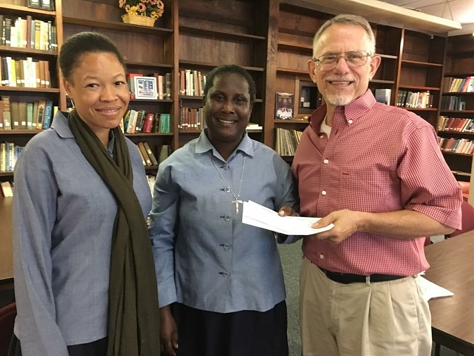 Dr. Gosser handing over a grant to the Sisters of St. Antoine of Fondwa to open their health care clinic.