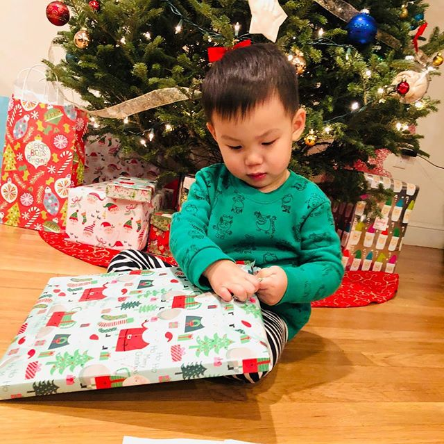 Christmas came a little early! We allowed him to open some presents to get him excited and see how he would react now that hes a little older. Only my child would be more concerned about placing the teared up wrapping paper in a neat little pile than opening his gift. 🤦🏻‍♀️🎄🎁📒 . . . . . #ouiouibebe #christmastree #christmaseve #presents #neatfreak #welovebooks #books #reading