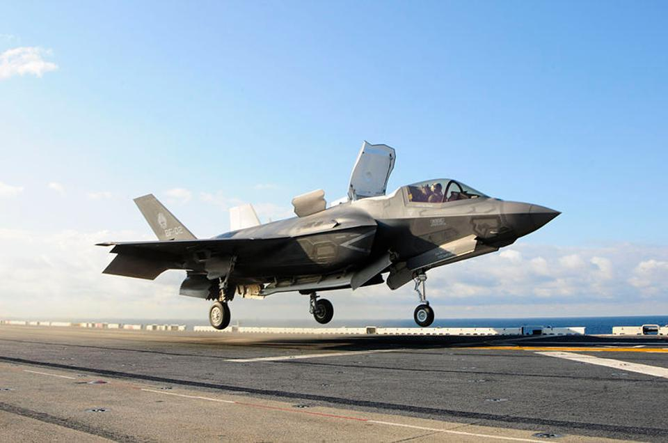 A Marine F-35B fighter lifts off from the deck of the amphibious assault ship USS Wasp. The open hatch behind the cockpit enables air to flow through a mid-fuselage lift fan; that plus downward-vectored engine nozzles at the rear give the plane vertical lift so it can land pretty much anywhere.  Image from Wikimedia