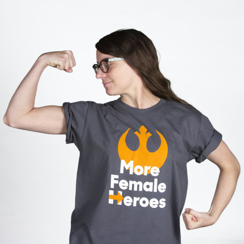 """A woman flexing, wearing a t-shirt with the  Star Wars  Rebel Alliance sign and the phrase """"More Female Heroes."""" The """"H"""" in """"Heroes"""" is Hillary Clinton's campaign insignia."""