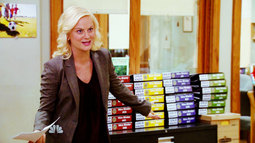 An image of Amy Poehler as Leslie Knope in  Parks and Rec , gesturing towards many color-coded binders.