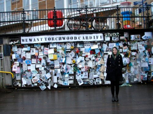 Elizabeth standing in front of the Torchwood fan shrine—a wall covered in Torchwood posters and so on—in Cardiff