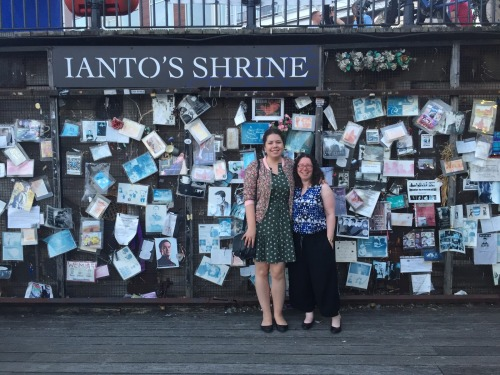 Elizabeth and Dr. Naomi Jacobs standing in front of Ianto's Shrine, a wall covered in flyers and photographs fans have tacked up commemorating Ianto from  Torchwood .