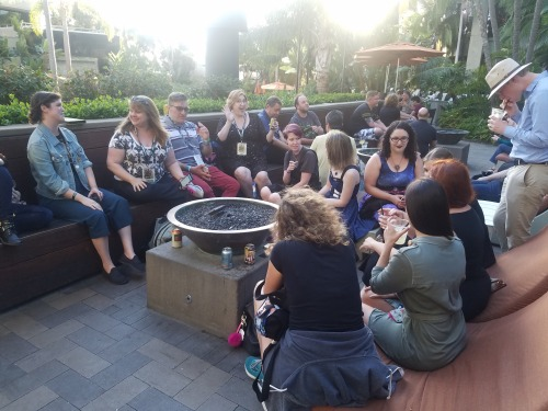 About 11 people gather around an outdoor fire pit at the San Diego Marriott, drinking and chatting.