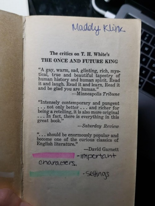 "An old paperback copy of T.H. White's  The Once and Future King , open to the front matter (laudatory quotes). The name ""Maddy Klink"" is written in a childish hand in the top right corner. A key is drawn in the blank space at the bottom of the page: pink highlighting denotes important characters, and green highlighting denotes settings."