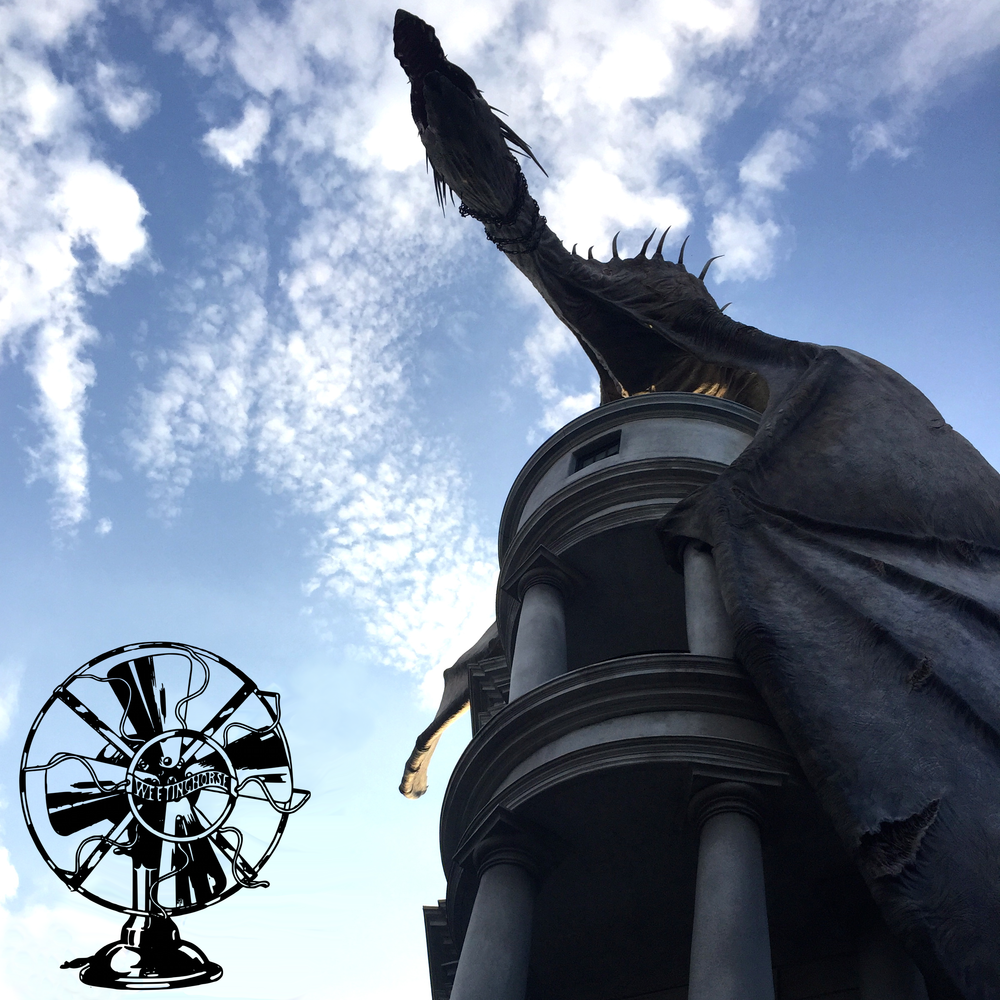 Episode 2's cover: Gringotts, at the Harry Potter theme park, seen from below, against a blue sky. A dragon crouches atop the building.