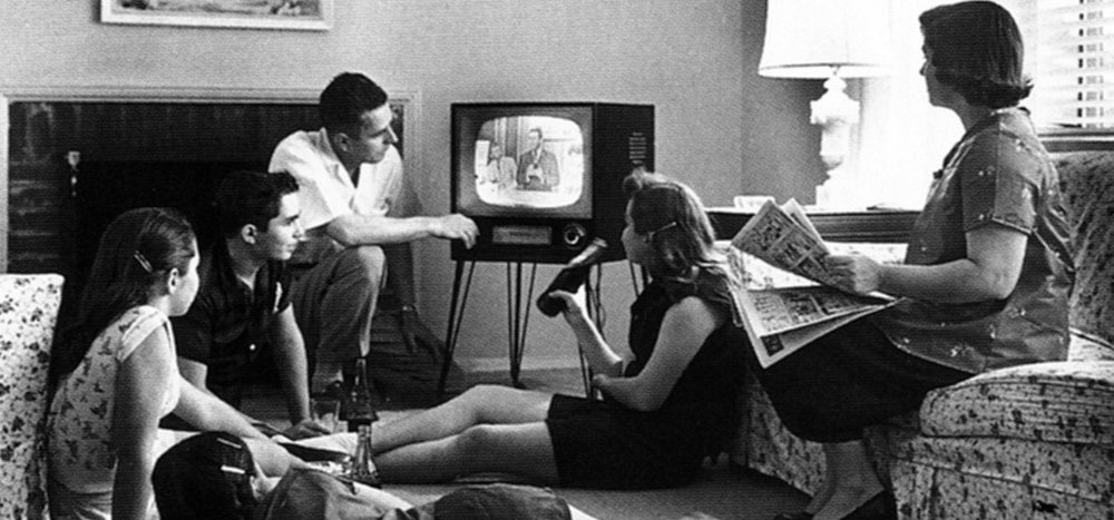 A 1950s family sits around and watches TV.