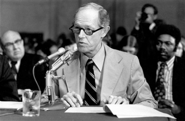 A man with a microphone in a tie, testifying before Congress.