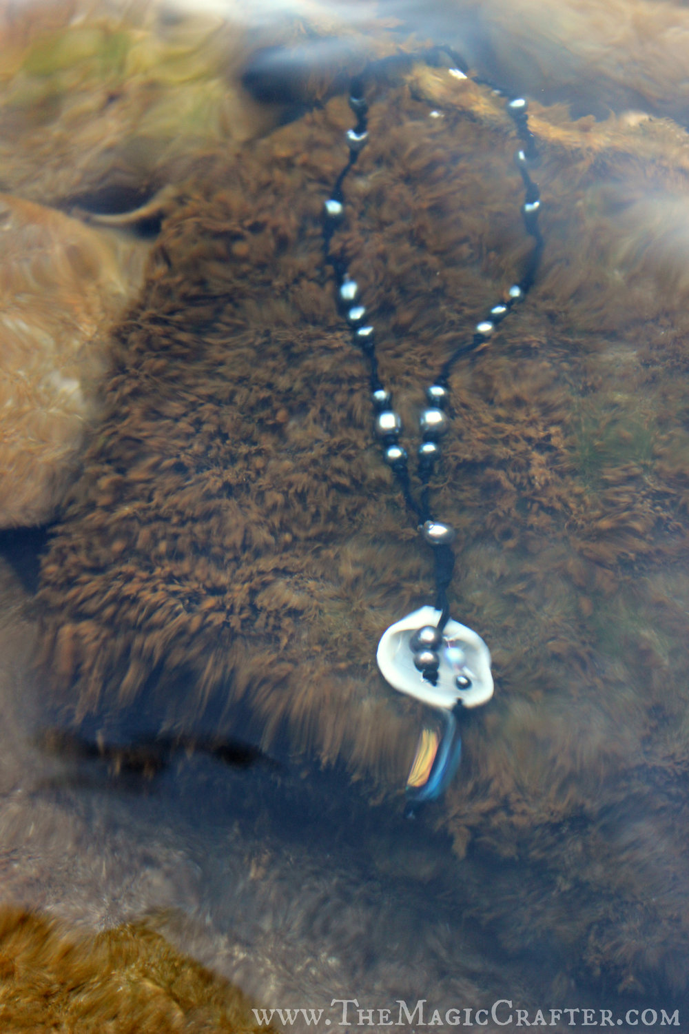 This photo is pretty blurry, isn't it? (They all are, actually... I'm about as stable on land as a ship out in a storm! XD) The blurriness is really because the necklace is underwater though. :D It's laying on a rather fuzzy rock near the shoreline of Grand Traverse Bay. It looks really pretty underwater!