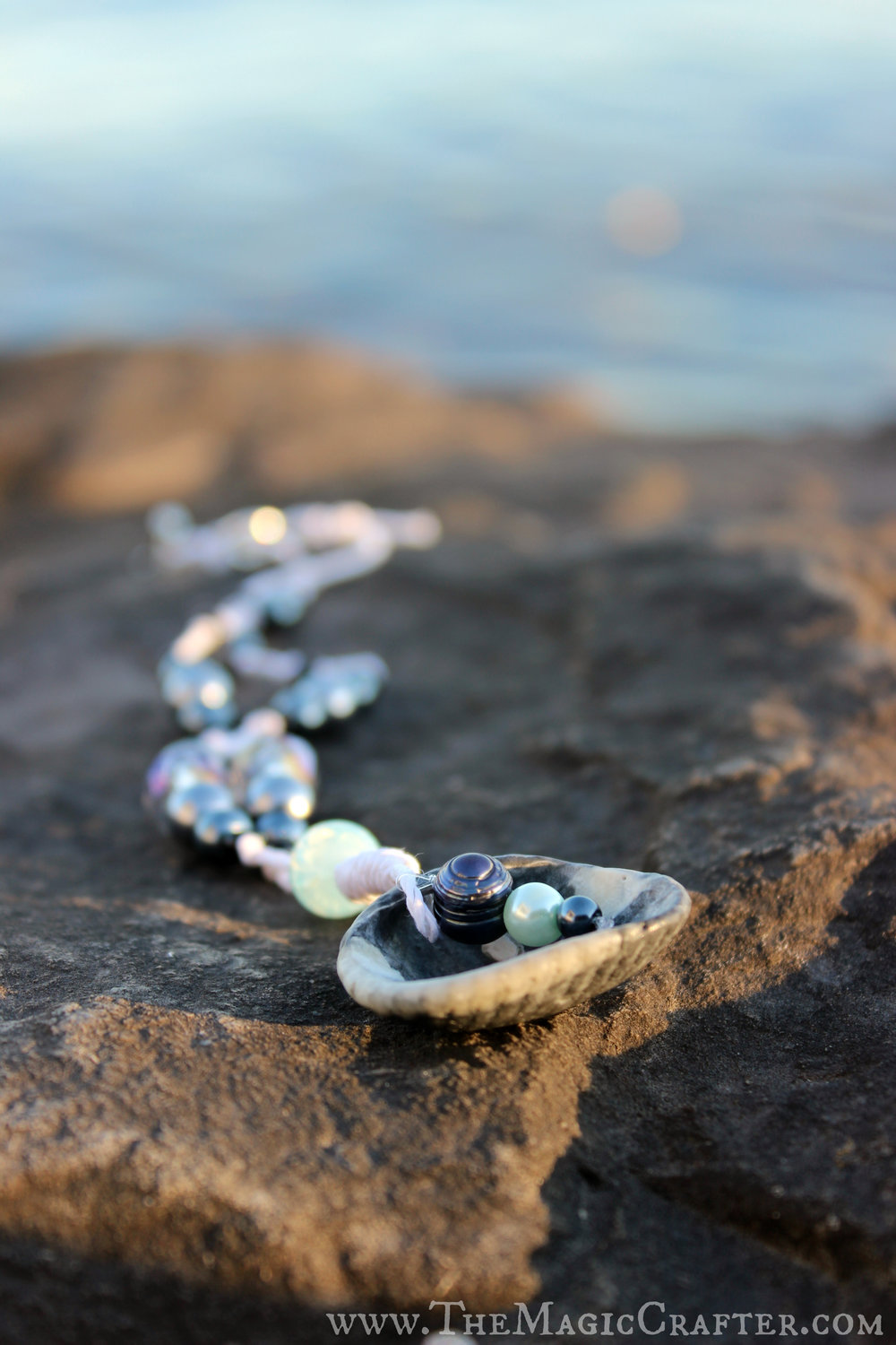 Here the shell necklace is soaking up some of the last of the sun's rays for the day. You can't really tell in this picture here, but the two purple-tinted gem beads that add an accent to the piece sparkle quite brilliantly in the sunlight!