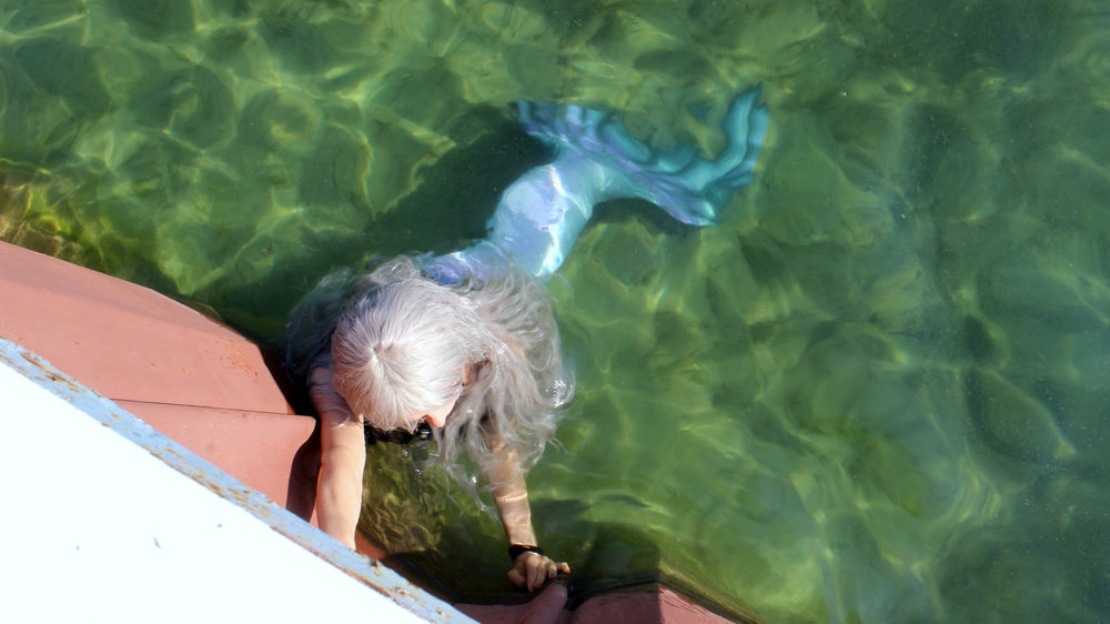 A mermaid was found alive swimming in the water of Grand Traverse Bay, near Traverse City, Michigan. Her tail was noted to be primarily silver with a some hints of purple and black as well. Her hair was silver and wavy like the white-caps of the waves on a windy day.