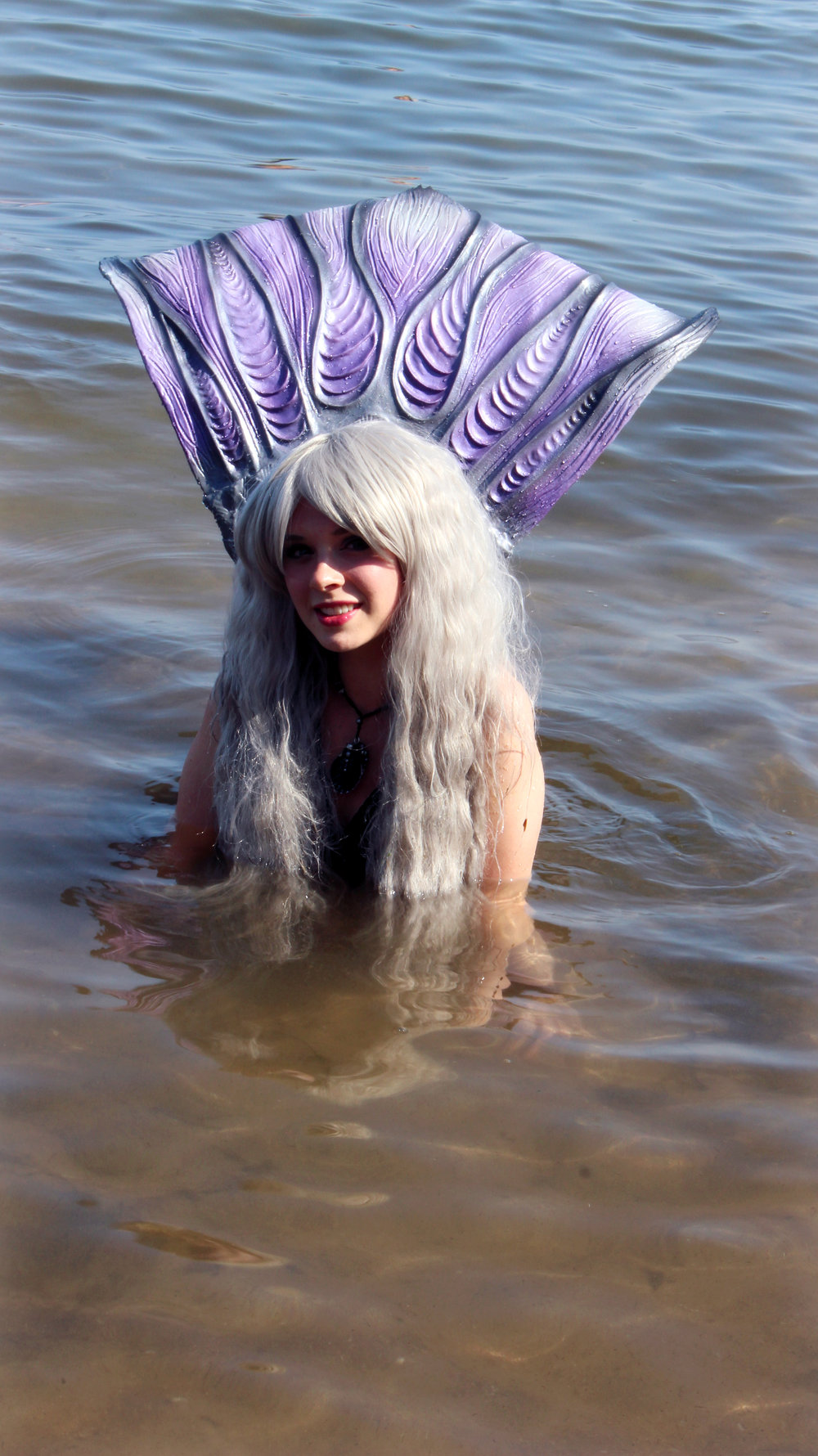 Mermaid Phantom, a real life Professional Mermaid, is holding her pretty tail high above her head. She is smiling after having had a long day of play out in the sunny waters of Grand Traverse Bay, Michigan. You can learn more about meeting her at www.themagiccrafter.com