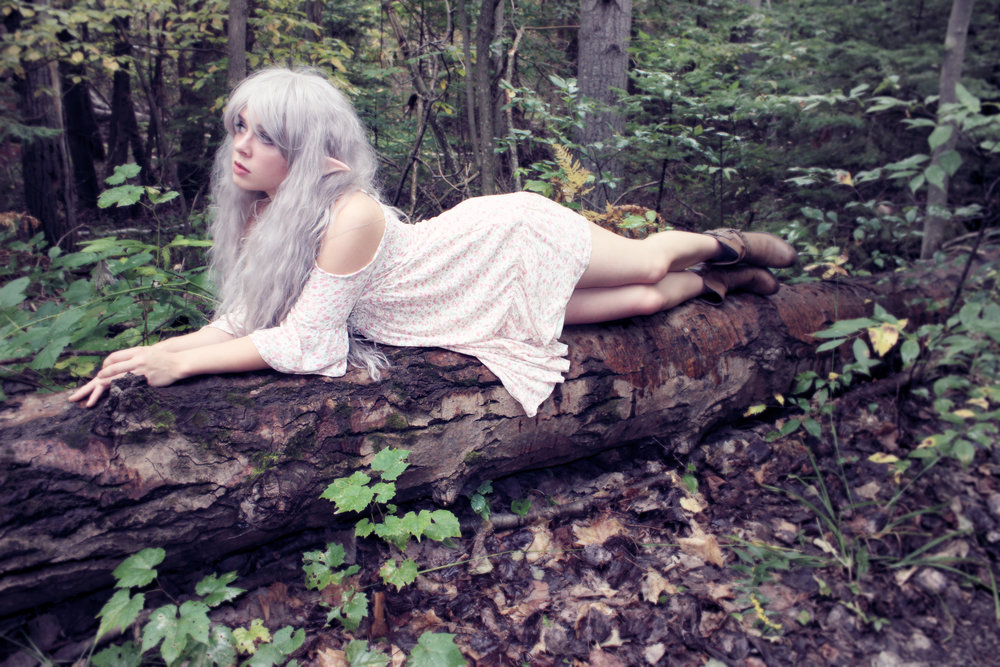 A female woodland elf, by the name of Phantom, is resting on a log in the forest. Her silver hair and pointy ears make it clear that she is not a human. However... she is not an elf by default. Phantom is a Professional Mermaid who sometimes transforms into other fantasy creatures with her magical cosplay magic!
