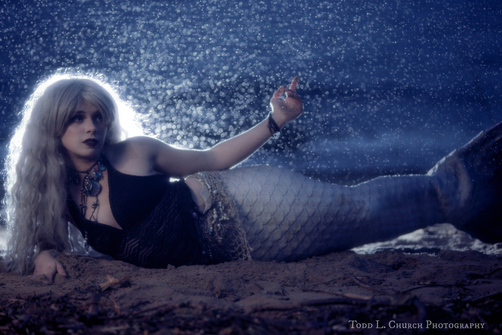 Rain Photography at Night: Pictures of a Mermaid in the Rain- Mermaid Phantom, a Professional Mermaid with a Silicone Mermaid Tail, can be seen laying on the beach playing in the rain. The picture was taken by Todd L. Church in Traverse City, Michigan, as an experimental nighttime photo shoot. Photo by: Todd L. Church Photography, Model: Mermaid Phantom of www.themagiccrafter.com