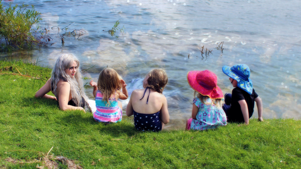 Meeting a real mermaid... Mermaid Phantom can swim up from out of the lake to meet and greet children and special guests in the warm-weather seasons. Here, she sits with a group of four children as they ask questions about life as a mermaid.