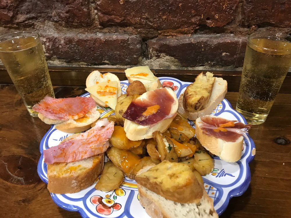 A selection of tapas. The patatas bravas are the potatoes covered in hotsauce at the bottom.