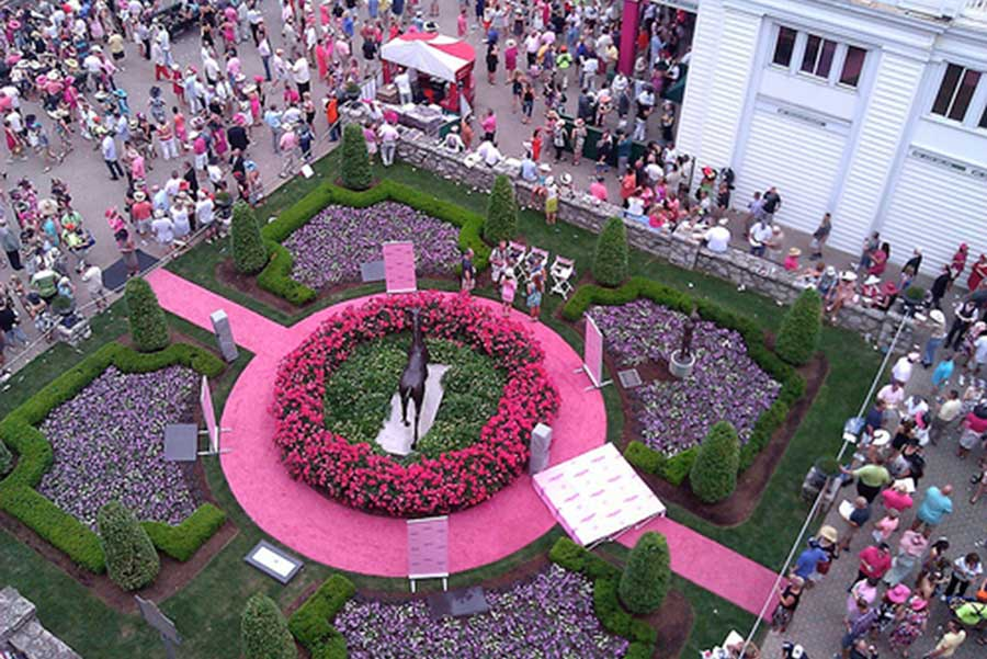 the paddock area at churchill downs is alive with pink on kentucky oaks day
