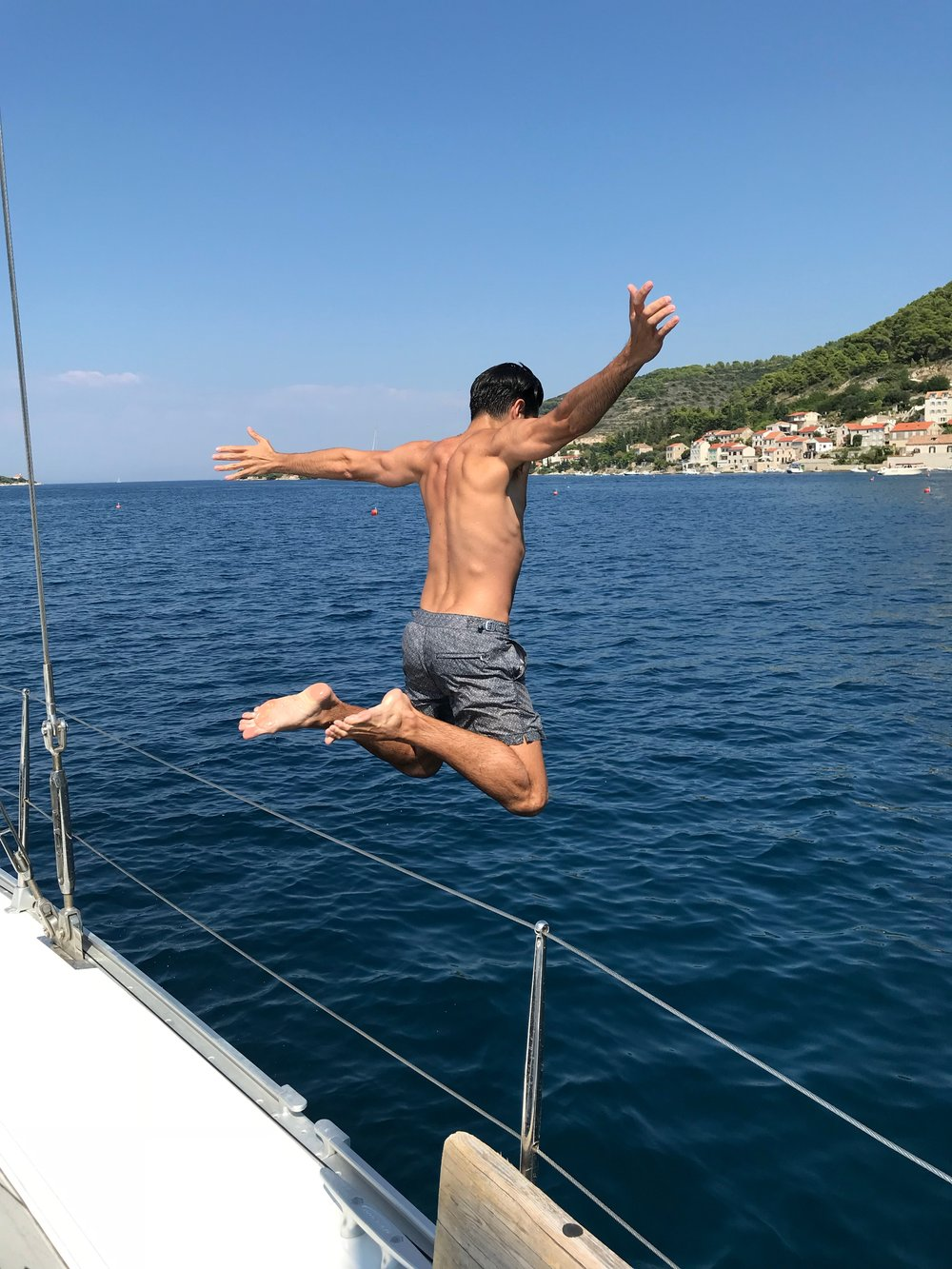 Designer jumping off boat into sea
