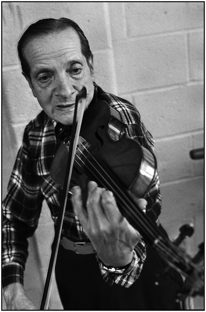 "Senior citizen practices violin. Shorefront ""Y.""  Coney Island Avenue and Brighton Beach Boardwalk. March 22, 1987"