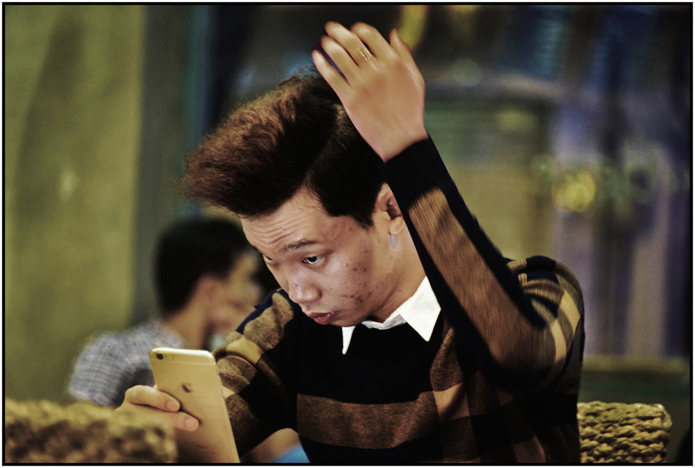 Young man primps using his smart phone, Caffe Bene, Saigon/HCMC, Dec. 2015. #5904