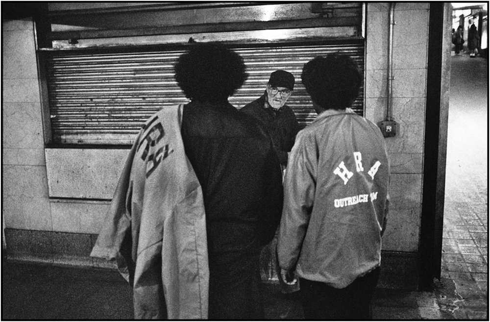 Human Resources Administration workers reach out to homeless man at Grand Central Terminal, Manhattan. 1989.