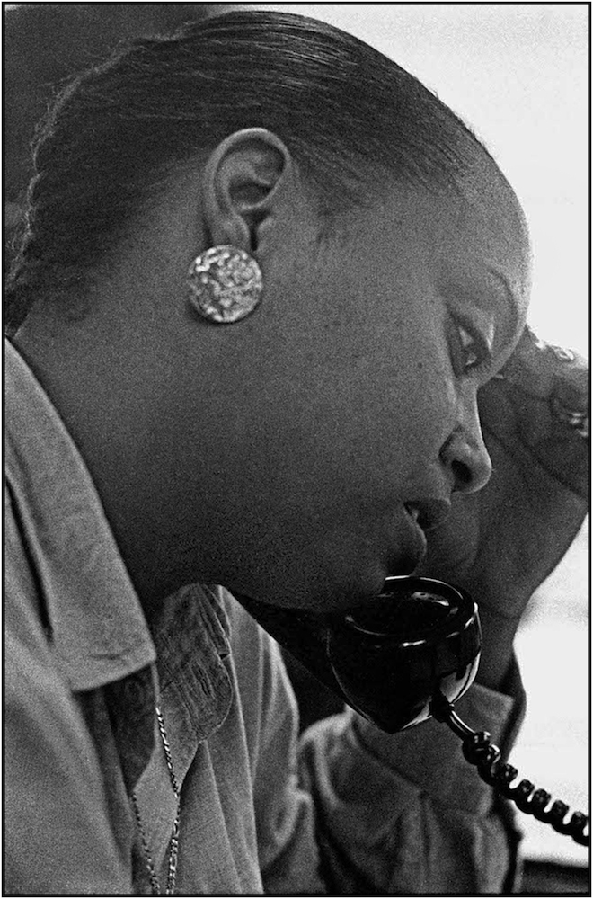 An eligibility specialist at the Bergen-Willis Income Maintenance Center in The Bronx, gives a welfare client  telephone assistance. 1988.