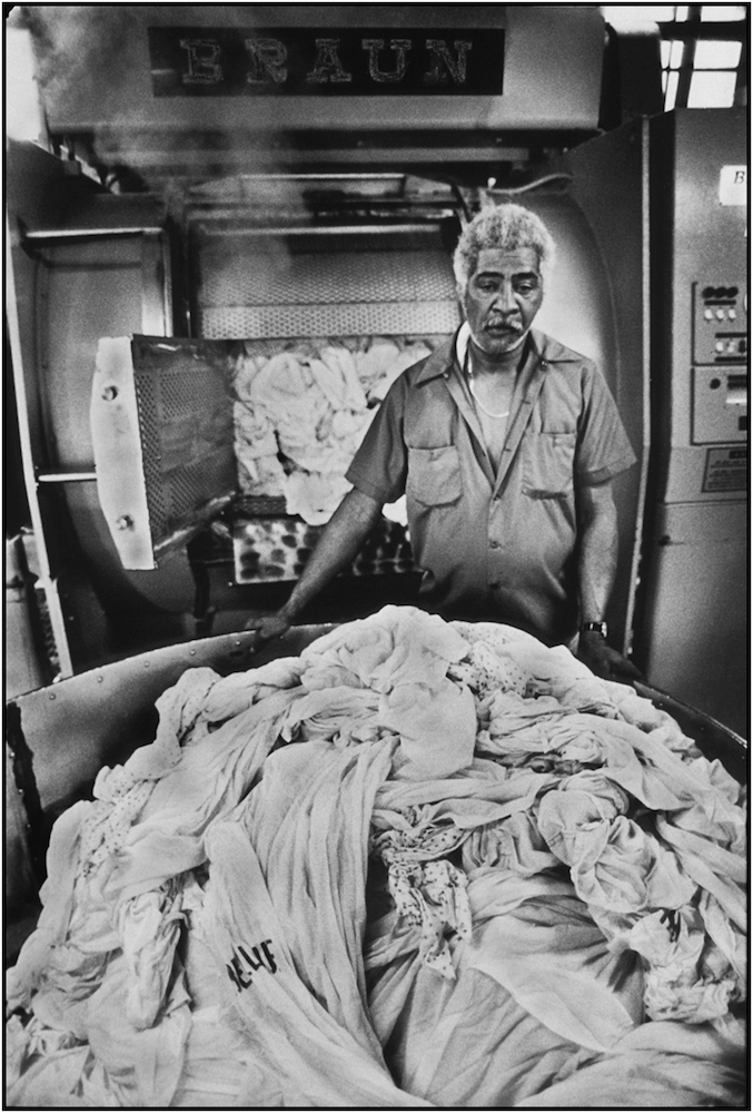 Laundry worker Jose Pedroso handles his share of six tons of daily wash at Bellevue Hospital, Manhattan. 1985.
