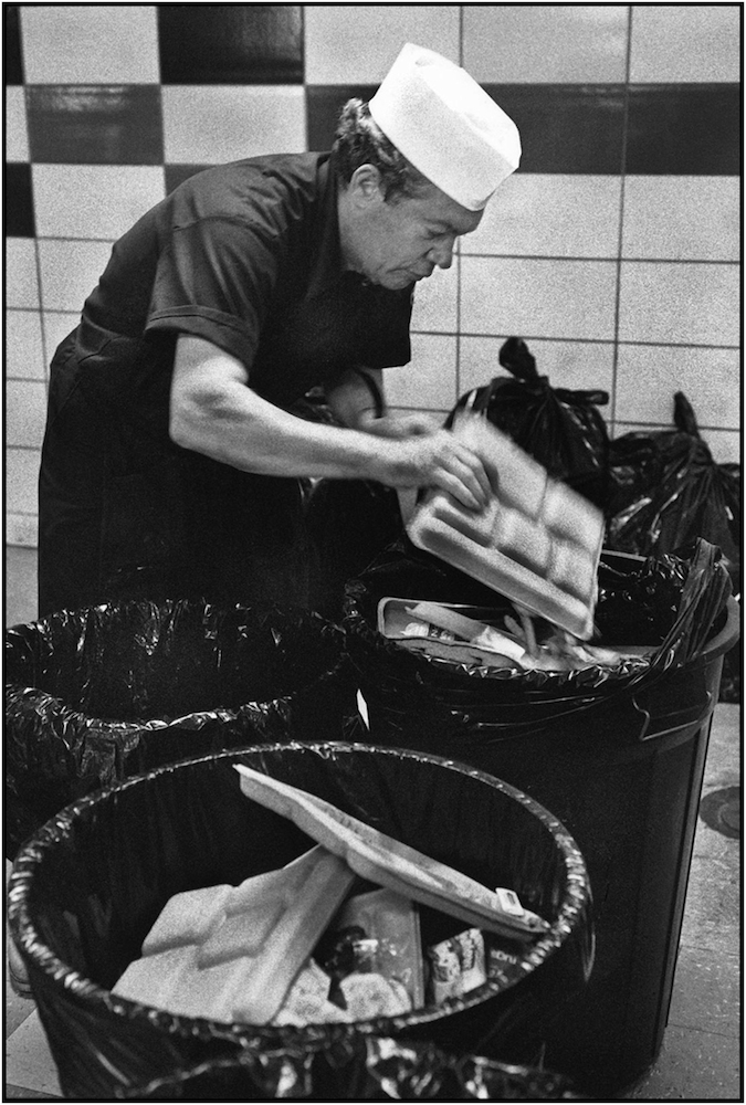 Board of Education, Office of School Nutrition Services workers Emanuel Palumbo collecting garbage in cafeteria, Manhattan. 1991.