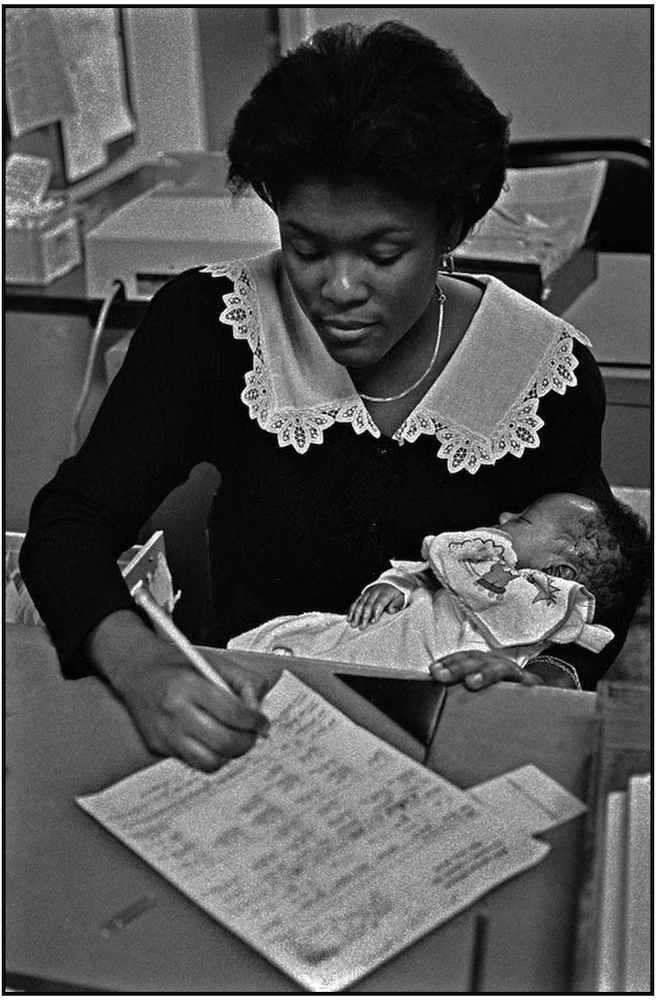 Office Aide Kettly Aime does her work while caring for child during mother's  examination at Kings County Hospital. 1988.
