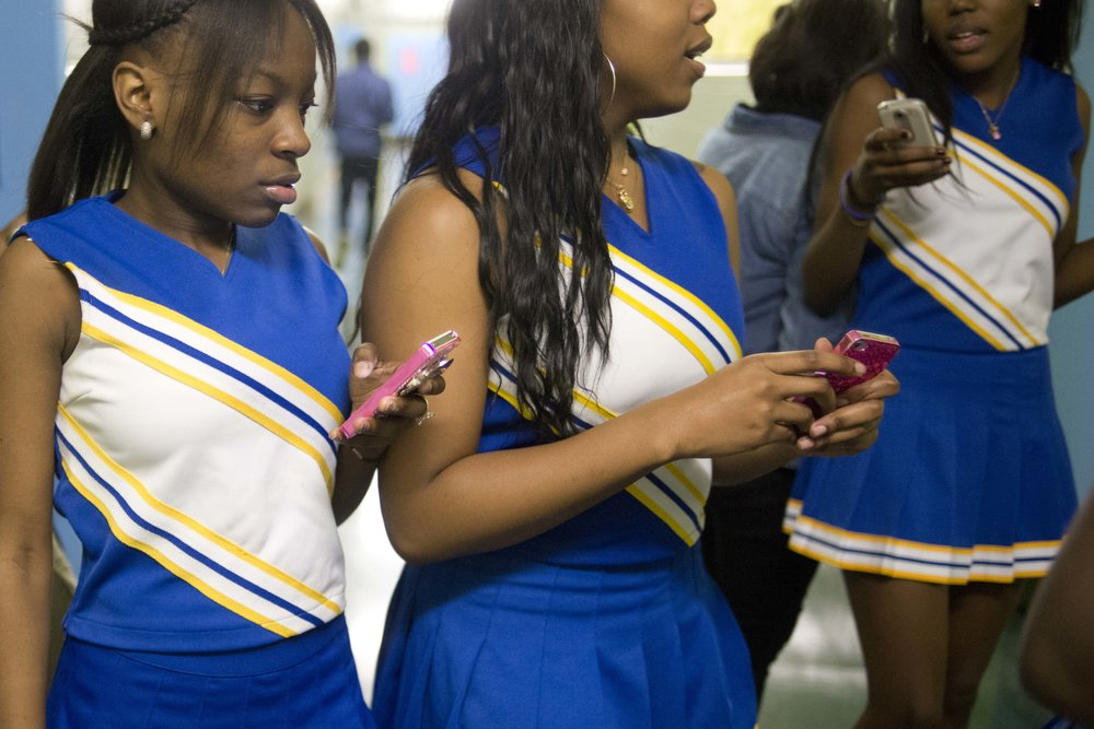 Lenasia Roper, a 12th grader, and her fellow cheerleaders take out their phones after a performance at a boys' basketball game at Brooklyn Community Arts and Media High School.