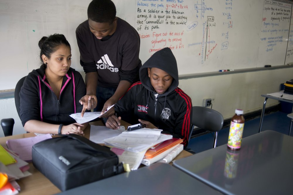 Jahlil Grant, right, and Charles Roberts, center, use their lunch break to receive extra math help from Ms. Bujan.