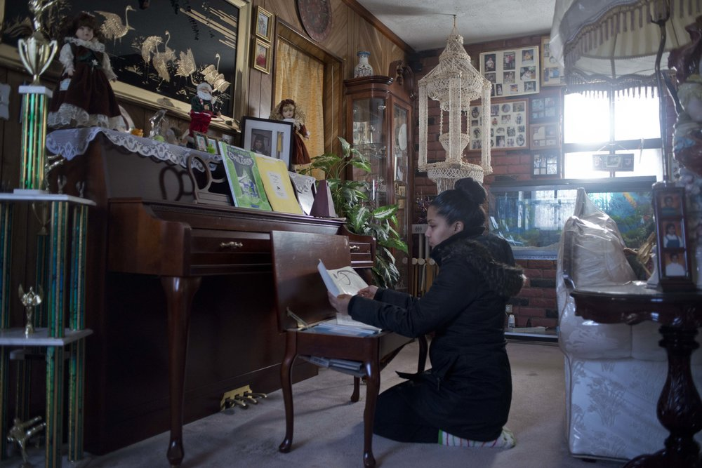 Ms. Bujan by the piano at her parents' house in Queens, NY. Her parents are West Indian, from Trinidad. She recently moved out of their house into her own apartment in Brooklyn.