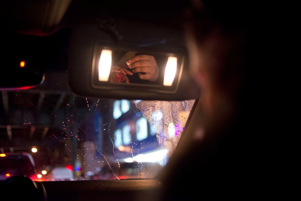 Ms. Bujan paints her nails in the car on her to meet some friends for a night out.