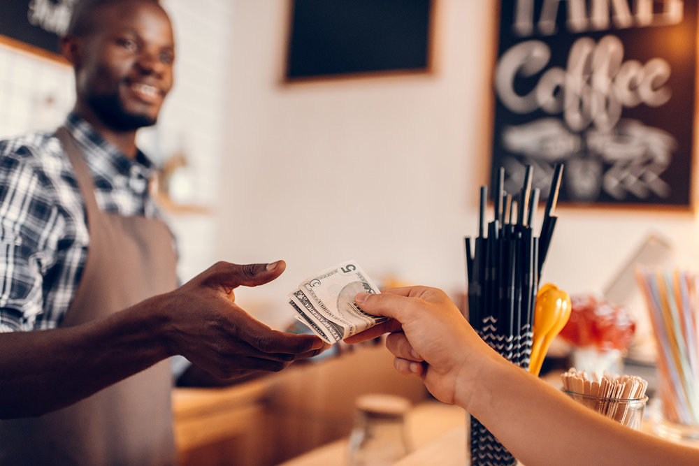 handsome smiling african american barista taking cash payment on