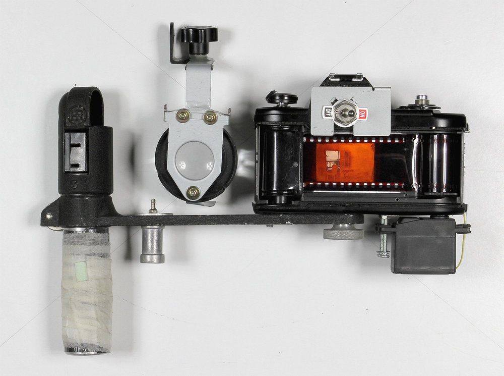 35mm Slide Film Viewer  2016.  Nikon EM body, flash bracket, modified servo motor, SPST switch, 2xAA battery holder, white LEDs, Holga macro attachment, SLR ground glass, metal pieces from a broken printer, nuts, screws, super glue.