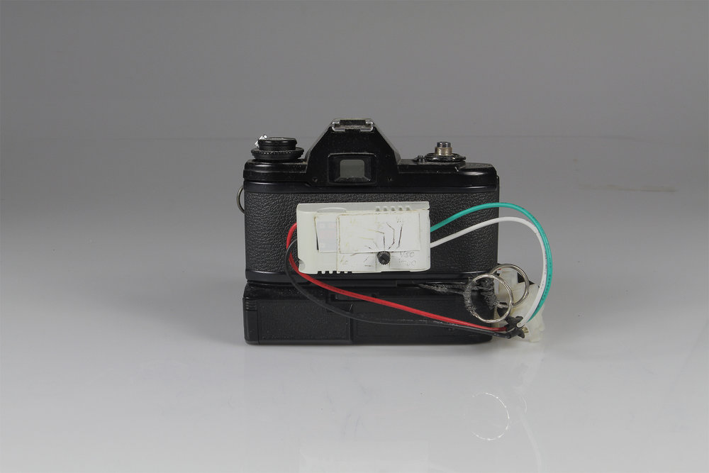 "Nikon Slitscan Camera  2014.  Modified Nikon EM SLR and Motor Drive for Strip Photography.  Nikon EM SLR w/ motor drive, pulse-width modulation circuit (motor speed control), black-rubberized 4x5"" film (to form the slit), electrical wire, wire connectors, key rings."