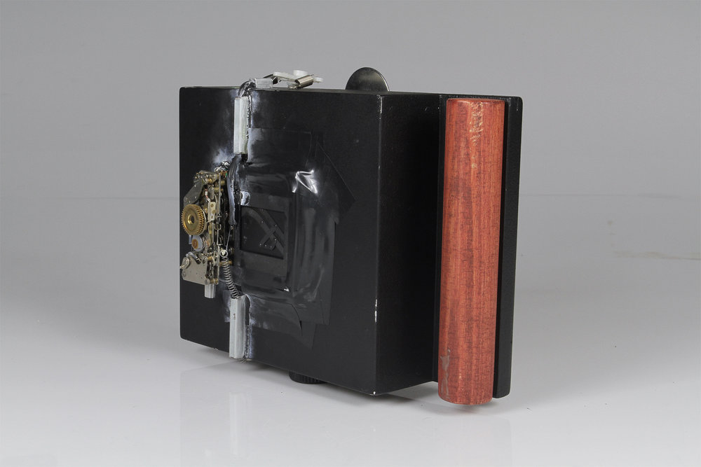 """ Copernicus Mk. III""    2016.  Modified pinhole camera for the series  Earth at 970MPH.   4x5"" Pinhole camera, salvaged mechanical SLR shutter, flash bracket, tripod head, air-rifle scope, welder's lens, springs and metal pieces from a broken printer, screws, black-rubberized soda bottle top, black caulk, electrical tape, epoxy."